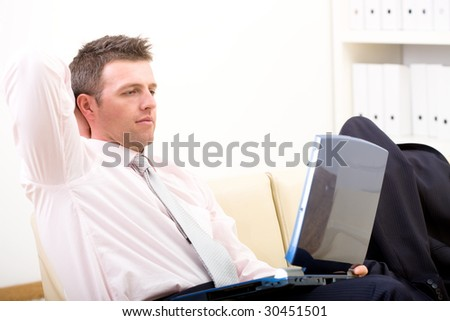 Relaxed businessman sitting at couch in office, using laptop computer, looking at screen. - stock photo