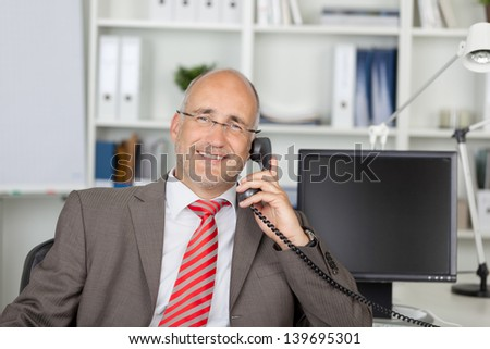 relaxed businessman sitting at desk and calling by phone - stock photo