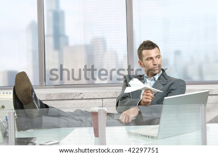 Relaxed businessman sitting at desk in front of office windows, playing with paper airplane, smiling. - stock photo