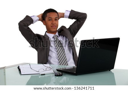 Relaxed businessman sitting at his laptop - stock photo