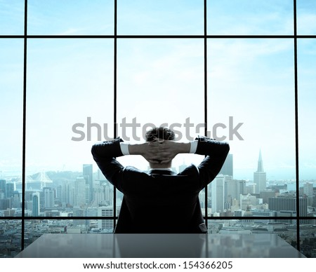 relaxed businessman sitting in office - stock photo