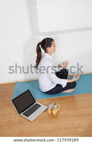 Relaxed businesswoman meditating in office during her lunch break - stock photo