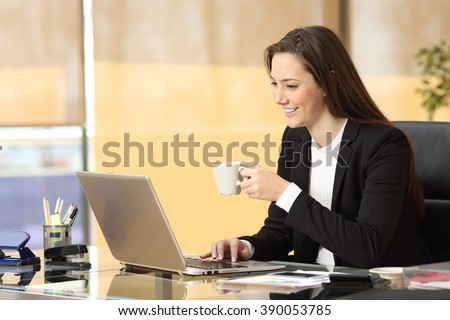 Relaxed businesswoman working online watching and browsing a laptop sitting in a desktop at office - stock photo