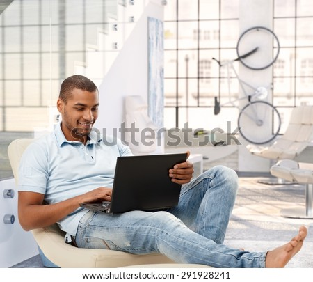 Relaxed casual afro american man browsing online with laptop computer at bright loft apartment. Sitting, barefoot, smiling, looking at screen. - stock photo