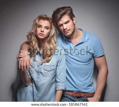 relaxed casual couple looking at the camera while posing in studio - stock photo