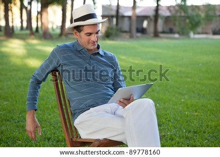 Relaxed casual man sitting in park using tablet PC - stock photo