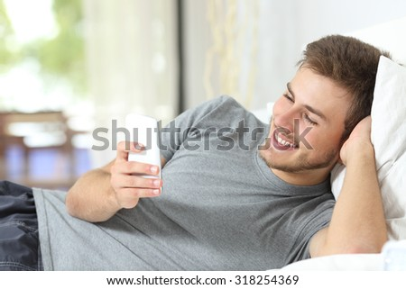 Relaxed casual man using a smart phone lying on the bed at home - stock photo