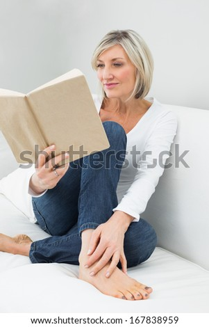 Relaxed casual young woman reading book on sofa at home - stock photo