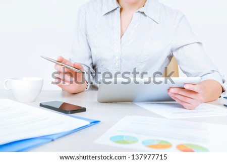 Relaxed caucasian businesswoman wearing casual shirt sitting at desk and working with data on digital tablet in the office