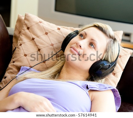 Relaxed caucasian woman wearing headphone lying on the sofa - stock photo
