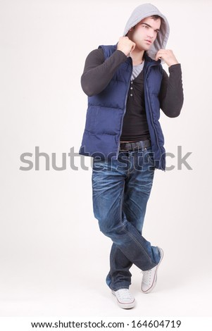 Relaxed charismatic young man in a hooded anorak top and jeans standing cross legged laughing at the camera, full length on white / Relaxed charismatic young man in a hooded top