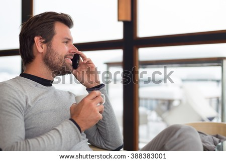 Relaxed charming man sitting in front of window with cup of morning coffee or tea near window chatting on phone. - stock photo