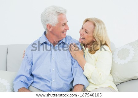 Relaxed cheerful loving senior couple sitting on sofa in a house