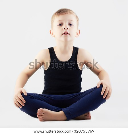 Relaxed child does yoga.handsome little Boy - stock photo