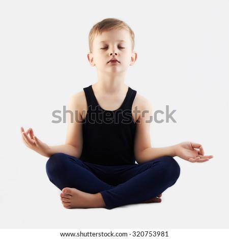 Relaxed child practicing yoga isolated on white background. little Boy does yoga - stock photo