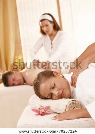 Relaxed couple having back massage in day spa.