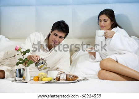 Relaxed Couple in Bed, hotel room - stock photo
