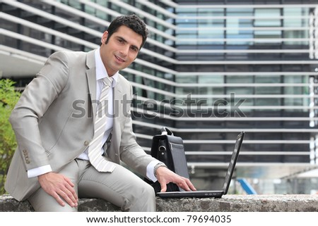 Relaxed director using laptop outdoors - stock photo