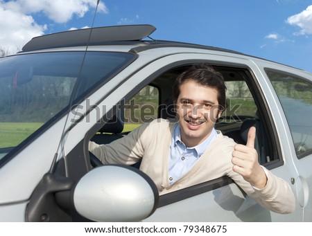 relaxed driver smiling on his car - stock photo