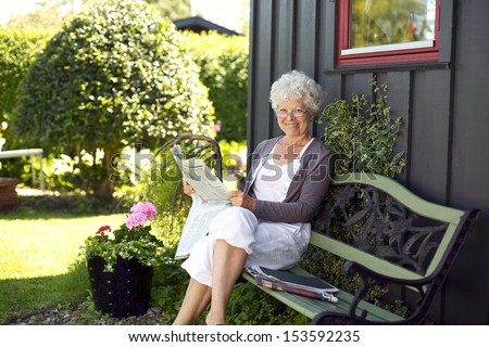 Relaxed elder woman sitting on a bench in backyard garden reading a newspaper looking at camera and smiling - stock photo