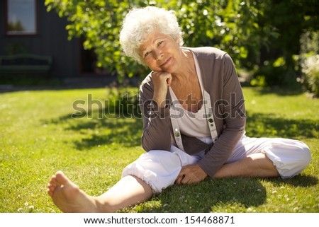 Relaxed elderly woman sitting on grass with her hand on chin looking at you. Senior woman sitting in backyard garden outdoors. - stock photo