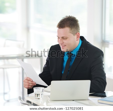 Relaxed executive sitting on desk in office