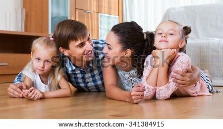 Relaxed family of four posing in the domestic interior  - stock photo