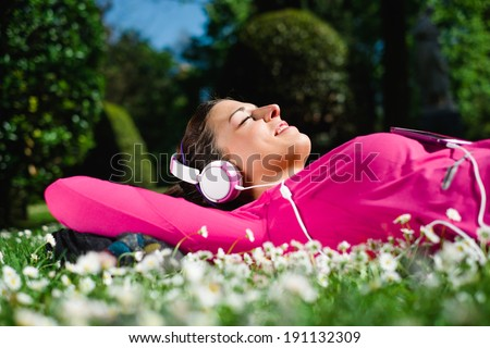 Relaxed female athlete resting and listening music with headphones after workout. Woman lying down and day dreaming on grass and spring flowers. Healthy lifestyle and happiness concept. - stock photo