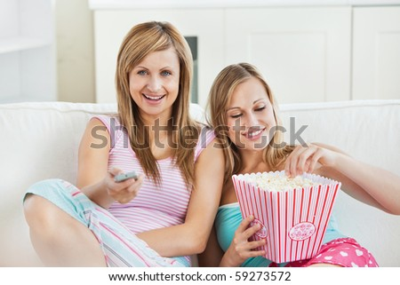 Relaxed female friends eating popcorn watching tv at home - stock photo