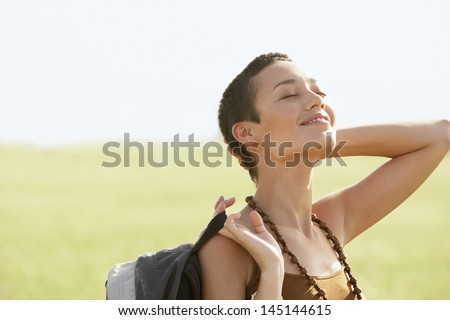 Relaxed female hiker basking in sun with eyes closed in field - stock photo
