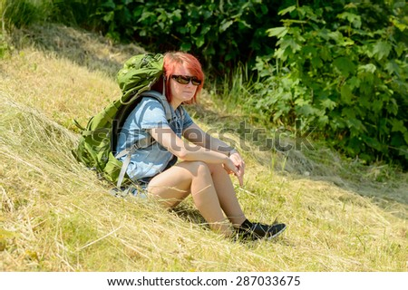 Relaxed female hiker taking a break in the grass one fine summer day. She has a green backpack and sunglasses.