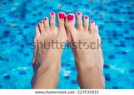 Relaxed female's feet against swimming pool water - stock photo