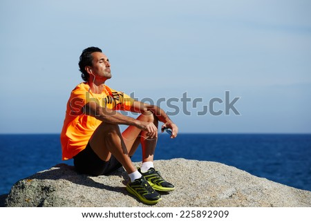 Relaxed fit man listening to music sitting on sea rocks outdoors, fit man in sportswear taking break sitting on rocks with sea horizon on background, rest and relax after the training, sport lifestyle - stock photo