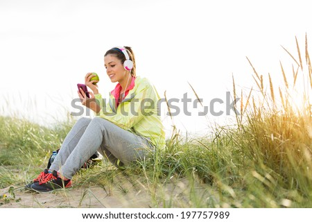 Relaxed fitness woman eating apple and texting sms on smartphone during a workout break at beach on summer sunset. Sporty girl relaxing after exercising. Playa de Xago, Asturias, Spain.