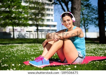 Relaxed fitness woman on workout rest on spring or summer. Beautiful fit girl in city park. - stock photo