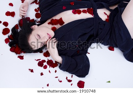 relaxed girl lying down with rose petals - stock photo