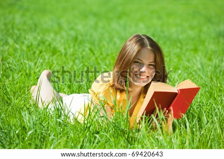 Relaxed girl lying on grass in meadow enjoying reading book
