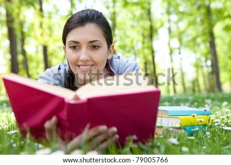 relaxed girl lying on grass in meadow enjoying reading book - stock photo