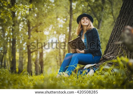 Relaxed girl reading an book under a tree
