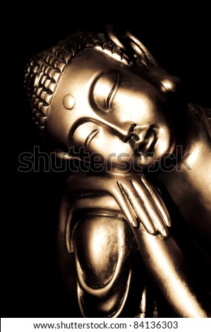 Relaxed golden buddha statue with a black background - stock photo