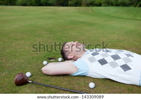 relaxed golfer lying on the green with hands behind head - stock photo
