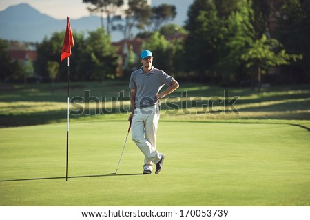 relaxed golfer standing on green with putter at sunset while playing 18th hole - stock photo