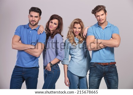 relaxed group of casual young people standing on grey studio background - stock photo