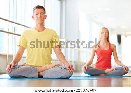 Relaxed guy meditating in pose of lotus with girl on background - stock photo