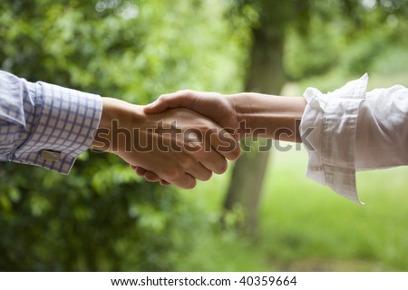 relaxed handshake in the middle of a garden - stock photo