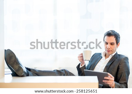 Relaxed handsome young businessman with his feet on the desk enjoying a cup of coffee as he reads his tablet computer. - stock photo