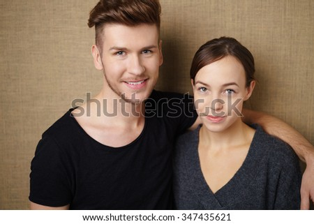 relaxed happy couple with arms around each other against light brown background - stock photo