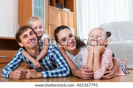 Relaxed happy family of four posing in domestic interior