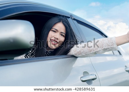 Relaxed happy woman on summer road trip travel vacation leaning out car window on blue sky background.