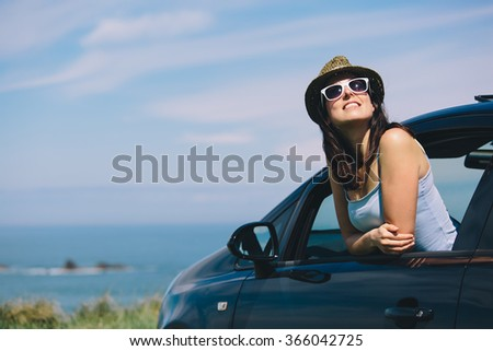 Relaxed happy woman on summer roadtrip travel vacation leaning out car window on blue sky background. - stock photo